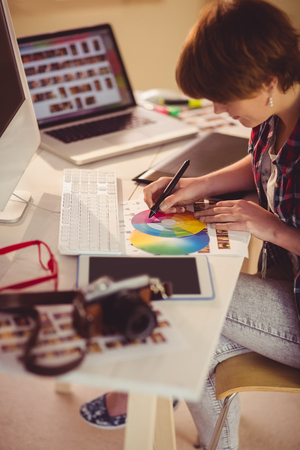 digitizer: Casual female designer working with digitizer and colour chart in office