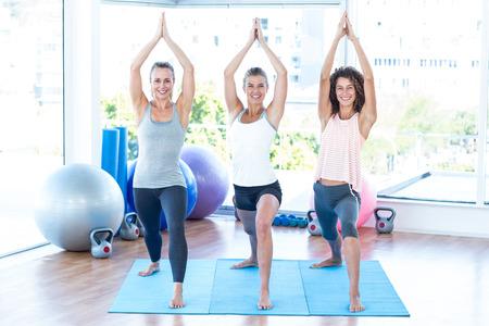 manos unidas: Mujeres felices con las manos juntas en el estudio de la aptitud mientras que estiran en la estera de yoga