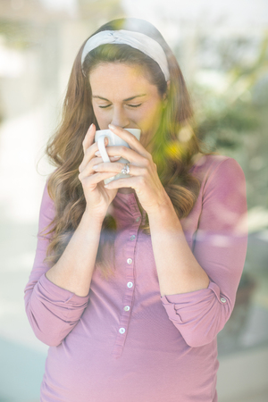 sipping: Pregnant woman sipping coffee from cup by window at home