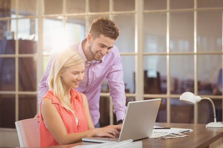 Smiling business people looking at laptop in creative office