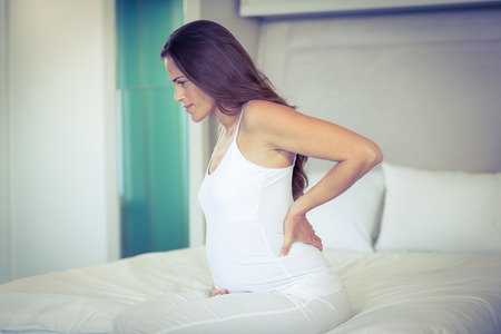 hand pain: Pregnant woman sitting with back pain on bed Stock Photo
