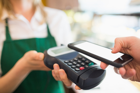 accepting: Cropped image of female worker accepting payment from customer through NFC in bakery