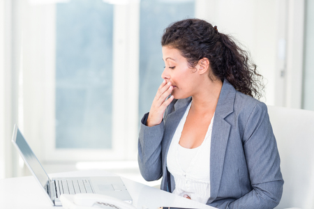 black pregnant woman: Tired pregnant businesswoman yawning in office Stock Photo