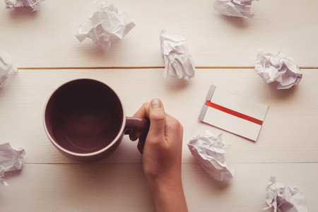 sticky hands: Hands holding coffee cup next to paper balls and sticky note in office