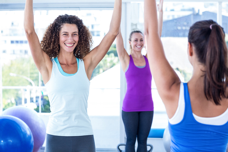 fit women: Cropped image of cheerful and fit women with arms raised in fitness studio