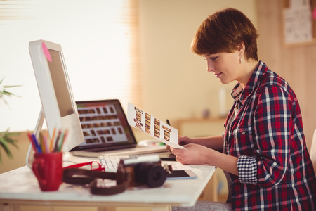 pics: Smiling photographer looking pics at her desk in office Stock Photo