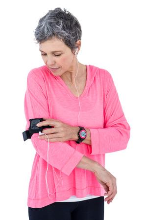 adjusting: Woman adjusting armband while listening music against white background