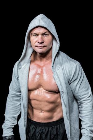 macho: Portrait of confident macho man in hood against black background