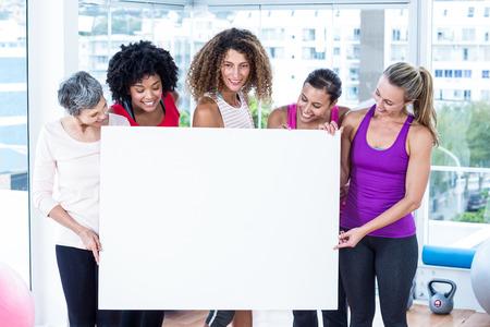 50s women: Smiling women holding board in fitness studio