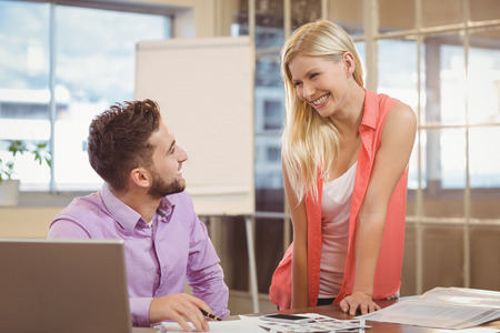 eachother: Happy business people talking to eachother by desk desk in creative office