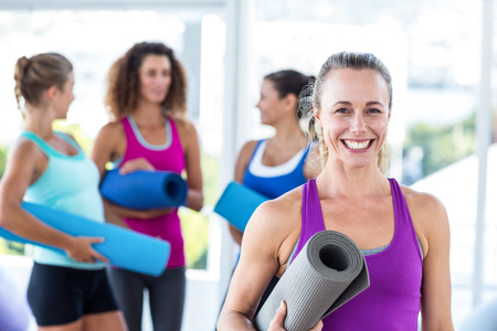 Portrait of cheerful woman holding exercise mat and smiling in fitness studio