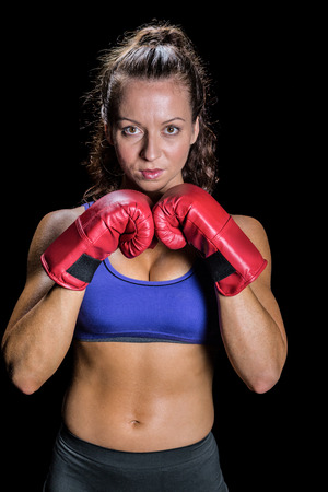 fighting stance: Portrait of pretty woman with fighting stance against black background