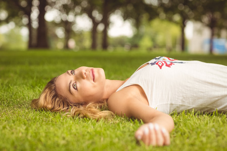 looking up: Beautiful woman looking up while lying on grass at park Stock Photo