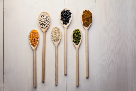 lima bean: Wooden spoons of pulses and seeds on wooden table Stock Photo