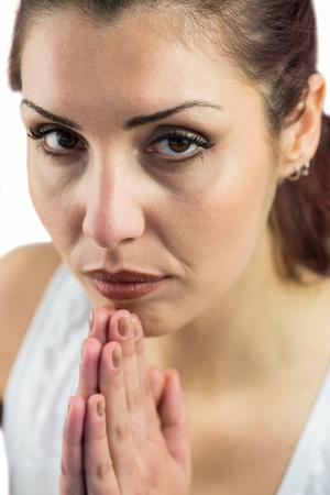 manos unidas: Retrato de mujer segura de sí con las manos juntas contra el fondo blanco