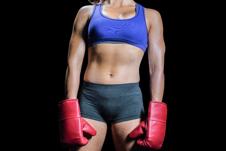 female boxer: Midsection of female boxer with gloves against black background