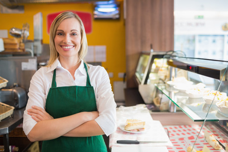 female: Portrait of confident female shop owner standing by display cabinet in bakery