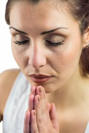 joined hands: Close-up de la mujer con los ojos cerrados y se uni� a las manos contra el fondo blanco