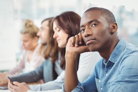 reunion de trabajo: Hombre reflexivo sentado en el escritorio con compañeros de trabajo en la oficina Foto de archivo