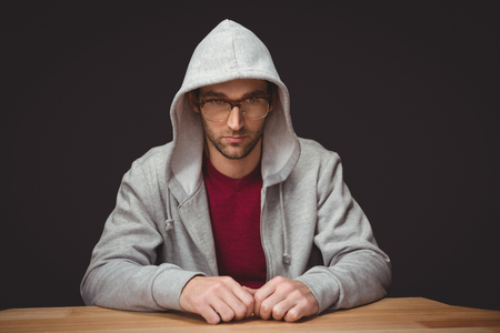hooded shirt: Thoughtful man with hooded shirt sitting at desk in office