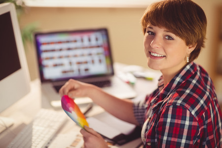 colour chart: Casual female designer smiling and holding colour chart in office