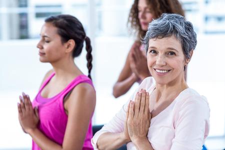 manos unidas: Retrato de la mujer feliz con las manos juntas en gimnasio