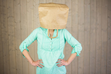 wall covering: Woman covering head with brown paper bag while standing against wall