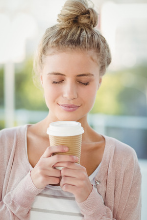 tempted: Tempted woman with eyes closed while holding coffee cup