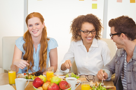 having lunch: Portrait of smiling businesswoman having lunch with colleagues in creative office Stock Photo