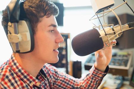 radio dj: Close-up of young radio host broadcasting in studio