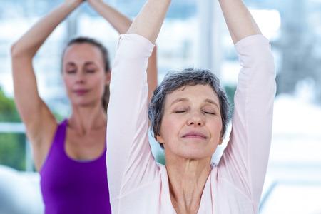 manos unidas: Las mujeres meditando con las manos y los ojos cerrados unidas en gimnasio Foto de archivo
