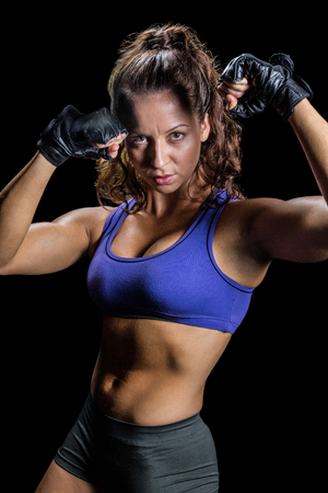 fighting stance: Portrait of confident boxer with fighting stance against black background