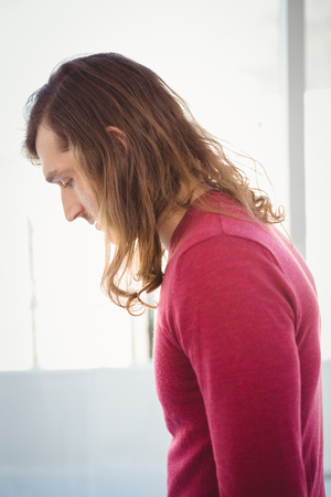 man looking down: Side view of man looking down while standing against window in office