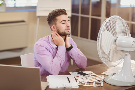 electric fan: Relax businessman with eyes closed sitting at desk with electric fan in office Stock Photo