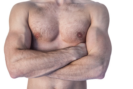muscle toning: Midsection of a man with arms crossed over white background