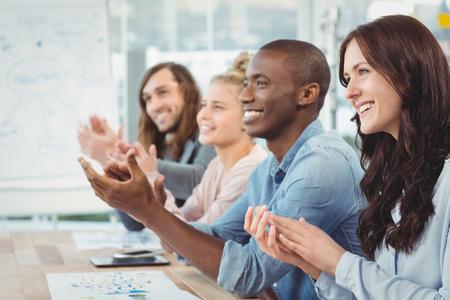 aplaudiendo: Sonriendo gente de negocios que aplauden en escritorio en la oficina