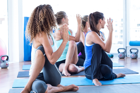 Fit women in fitness studio doing spine twisting pose on exercise mat