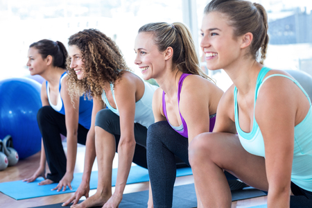 lunge: Cheerful woman in fitness studio doing lunge pose on exercise mat