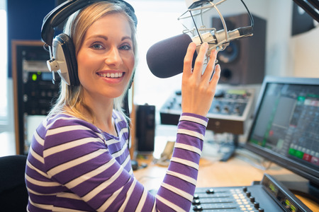 host: Portrait of happy young female radio host broadcasting in studio Stock Photo