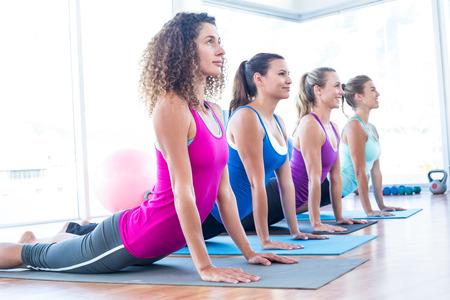 salud y deporte: Vista lateral de mujeres que realizan cobra plantean en el estudio de la aptitud