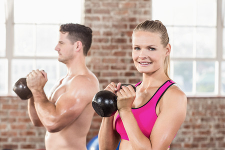 lean out: muscular smiling couple with kettlebells in crossfit gym