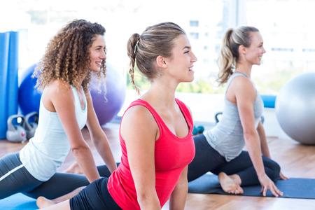 class room: Cheerful women doing pigeon pose in fitness studio