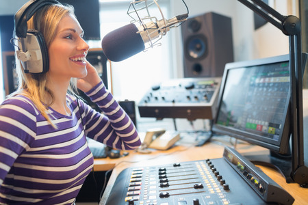 host: Close-up of happy female radio host broadcasting through microphone in studio