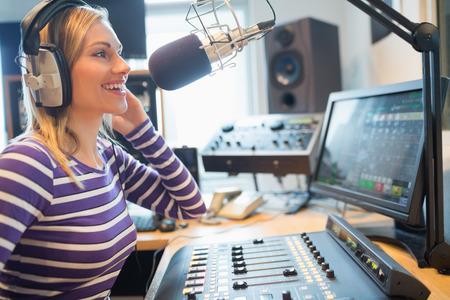 microfono de radio: Primer plano de feliz radiodifusión locutor de radio femenina a través de micrófono en el estudio