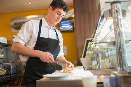 cuchillo de cocina: Ángulo de visión baja de sándwich de corte trabajador masculino en vitrina en la panadería Foto de archivo
