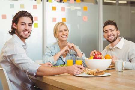business: Portrait of business people having lunch in creative office Stock Photo