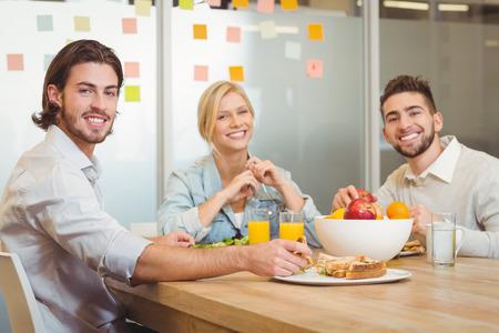 Portret van mensen uit het bedrijfsleven met een lunch in creatieve kantoor