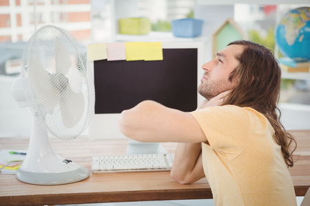 electric fan: Tired hipster sitting by electric fan on desk in office Stock Photo
