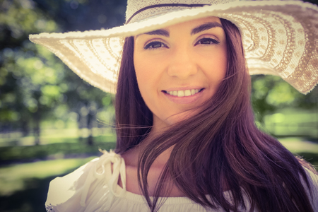sun hat: Portrait of smiling woman in sun hat while standing in park