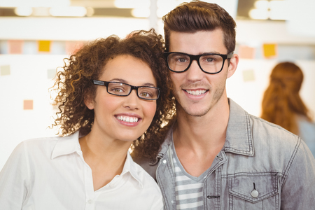 young adult man: Portrait of smiling business people wearing eyeglasses in creative office Stock Photo